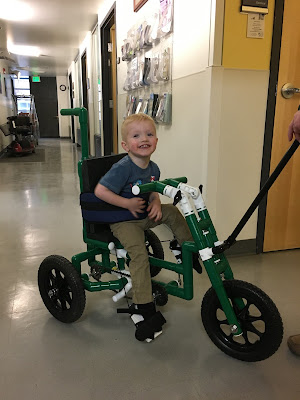a boy grins from a green PVC bike