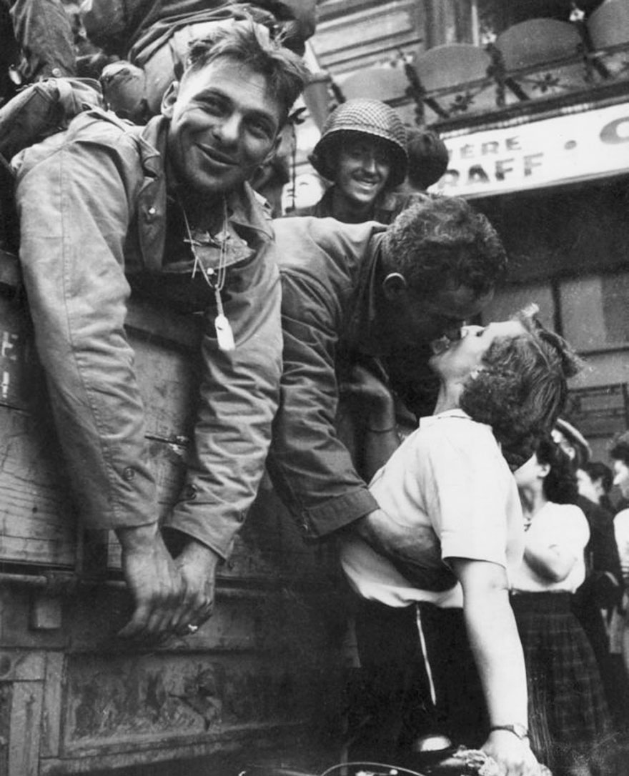 60 + 1 Heart-Warming Historical Pictures That Illustrate Love During War - An American Soldier Leans Over The Side Of An Army Vehicle As He Kisses A French Woman On A Bicycle During The Liberation Of Paris, 1944