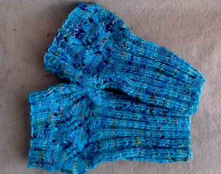 Two boot toppers laying flat.  They are knit with 2 by 2 ribbing in the round, and the top is done in a diamond lace pattern.  Yarn is blue with speckles of many colours.