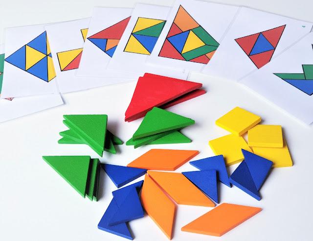 na obrazku widać kolorowe elementy tangramu rozsypane na stole, są to trójkąty, kwadraty i równoległoboki. na drugim planie widać karty pracy z wzorami przestrzennymi do odwzorowania