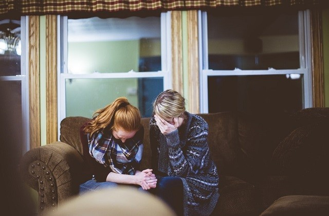 woman praying and counseling a girl