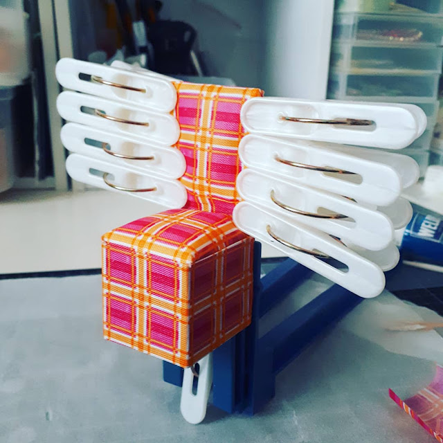 One-twelfth scale modern miniature chair kit with many clamps holding the edges together.