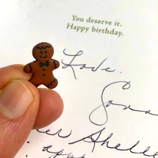 A small gingerbread man button in my hand, with Shelley's mom's card in the background.
