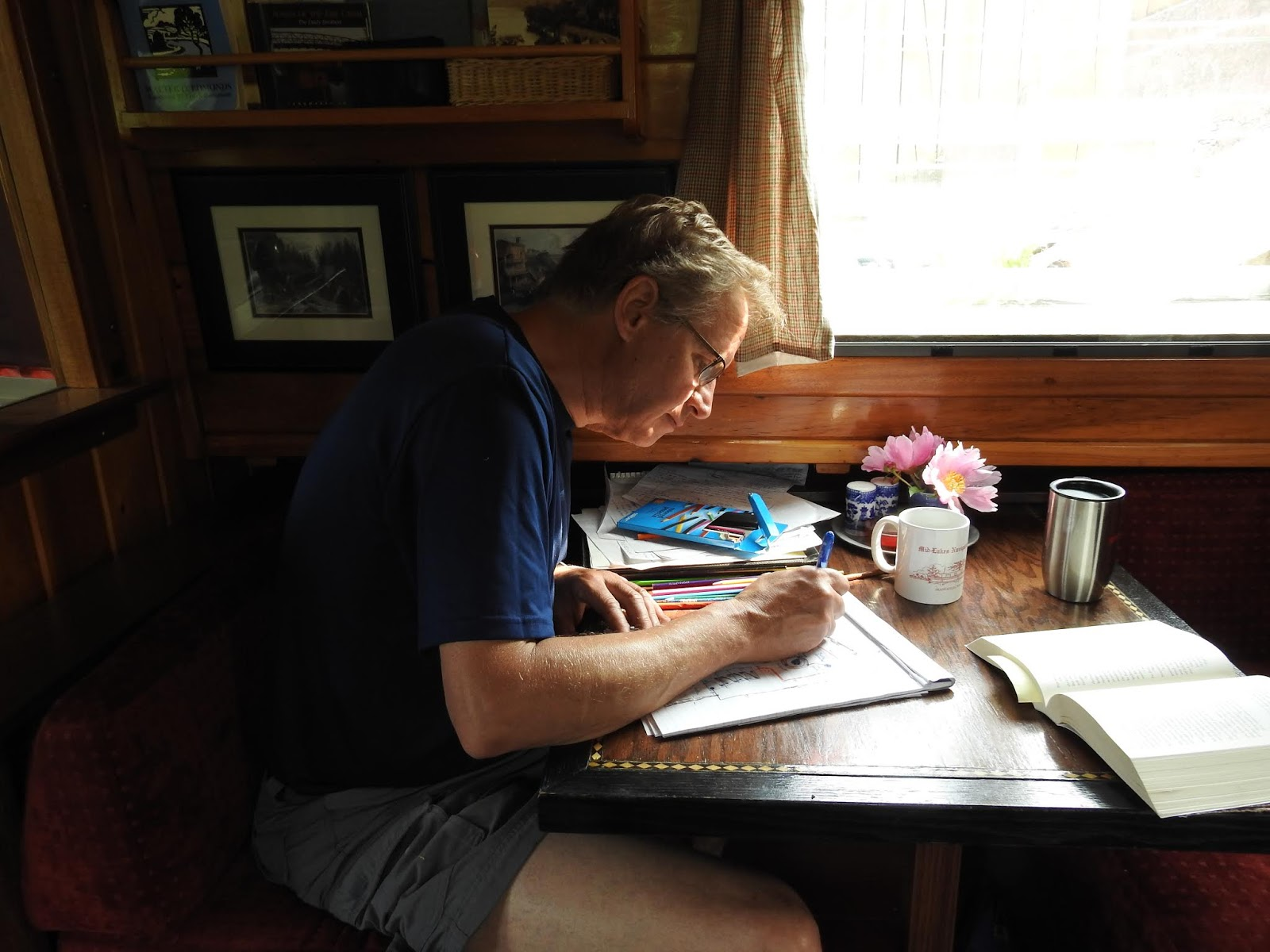 Bill Carlsen, captain of solar canal boat Dragonfly, works on wiring  diagrams