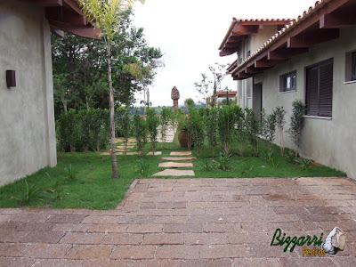Execução do caminho no jardim com pedras Goiás tipo cacão com calçamento de pedra folheta e a execução do paisagismo com o gramado com grama esmeralda em residência em Piracaia-SP.