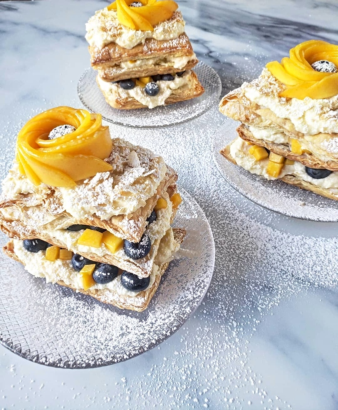 Stacked puffed pastry with buttercream, mango, and blueberries