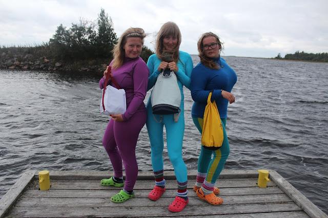 Kolme naista poseeraa laiturin päässä pitkissä kerrastoissa ja crockseissa eväsreppujensa kanssa kuin huippumallit