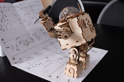 A wooden robot holding a screwdriver, studying a sheet of instructions that he is also standing on.