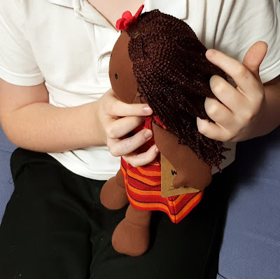 Boy playing with ghanaian multicultural doll