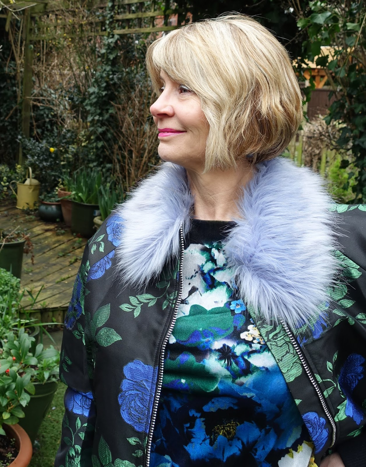 Close-up of blue and green faux fur trimmed floral bomber jacket from Asos