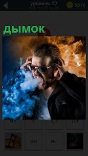 Мужчина курит в очках и изо рта идет дымок от сигареты, на ушах держит руками наушники