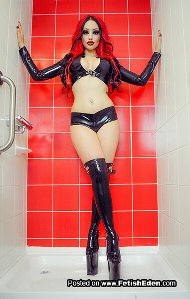 Dani Divine with red hair wears black latex shrug with black latex stockings