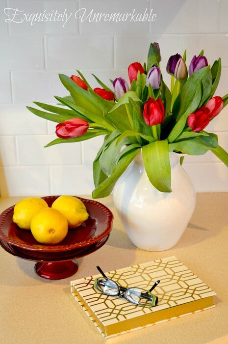 Kitchen Tulips next to cake plate with lemons and a journal on countertop