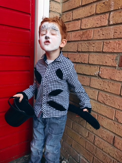 Little red haired boy with his face painted to look like a wolf, whilst wearing the made shirt