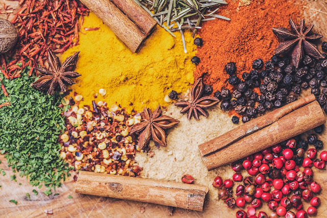 A plethora of autumn spices including cinnamon and turmeric spread out on a table