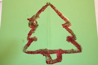 Postal com contorno de árvore de Natal feito de glitter, em cartolina verde