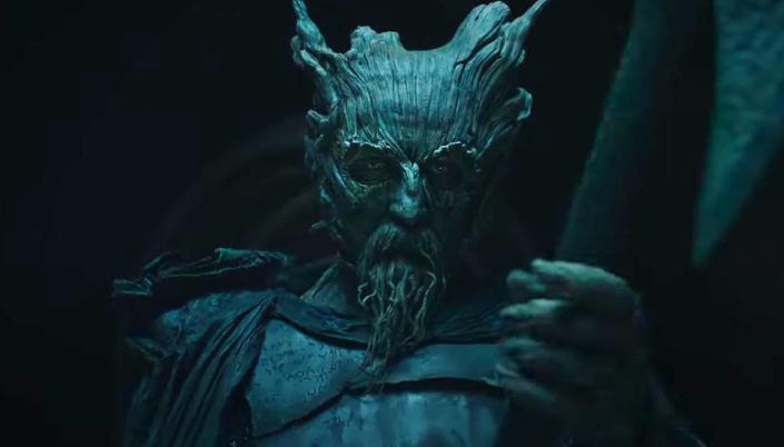 Imagem: o Caveleiro Verde, um ser humanóide com o rosto feito de madeira, usando uma capa escura e segurava um enorme machado num fundo escuro.