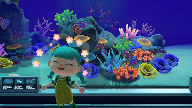 A screenshot from Animal Crossing New Horizons showing a happy character in front of a coral reef aquarium at the museum