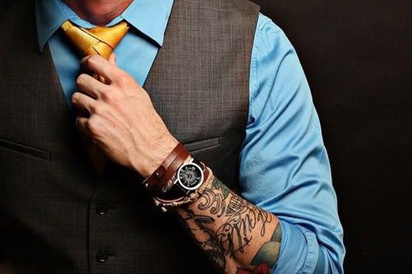 Vemos a un hombre trajeado con tatuajes en el antebrado