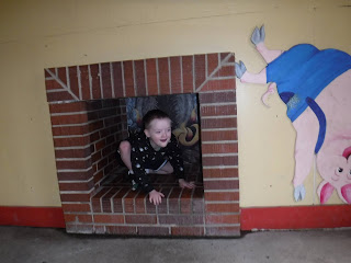 a boy crouches in a brick fireplace next to a mural depicting one of the three little pigs