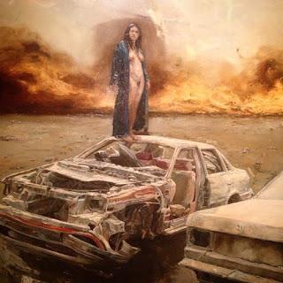 Una mujer desnuda posa de pie un   automóvil destruido en una tierra   desierta y en llamas. La mujer no   parece consciente  de lo que sucede a su alrededor. Obra parte de su   exposición Pies de Ceniza del artista   de Guadalajara, México, Sergio   Garval que encontré expuesta en   el Museo del Pueblo de Guanajuato.