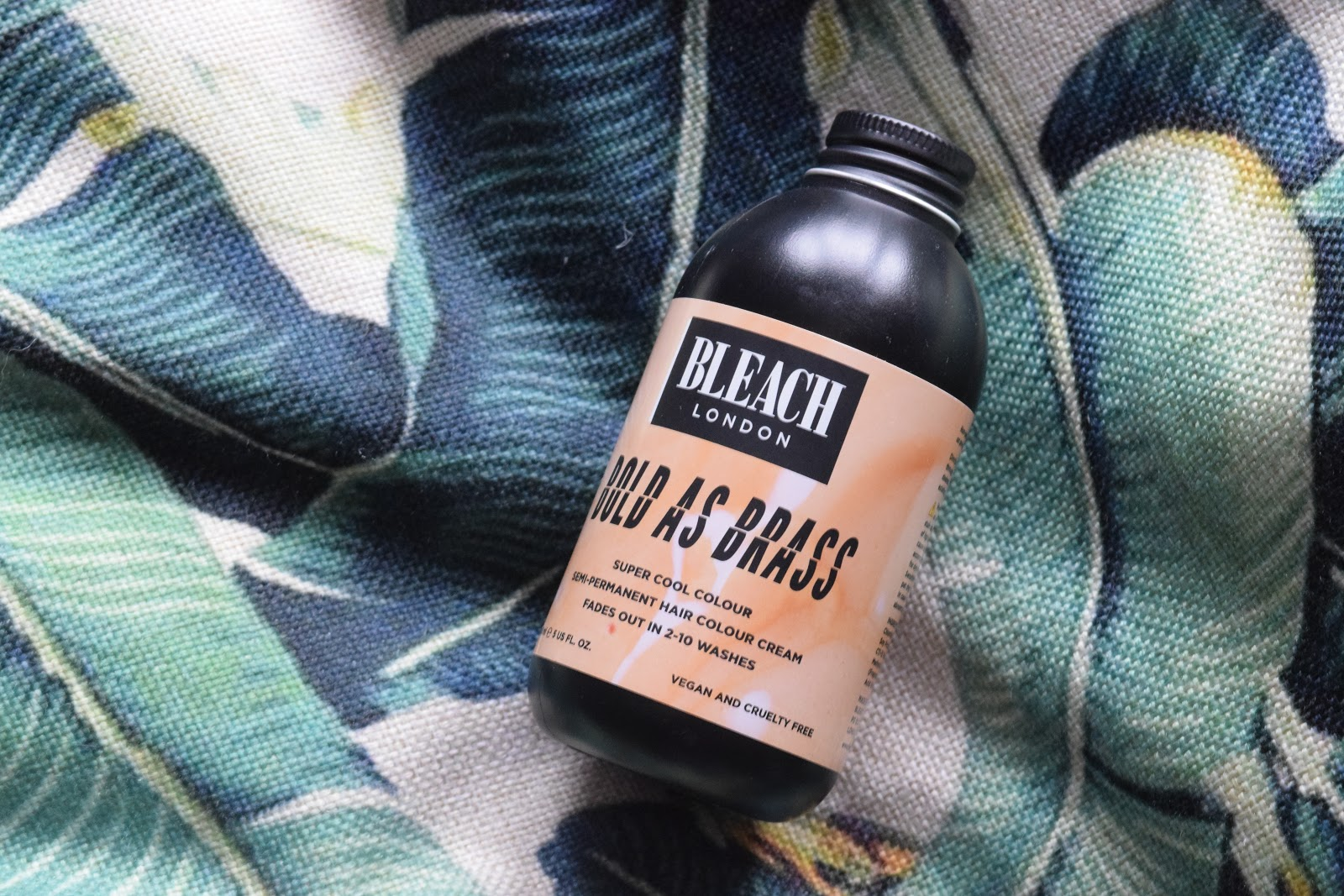 Bleach London bold as brass hair dye bottle on a leaf patterned background