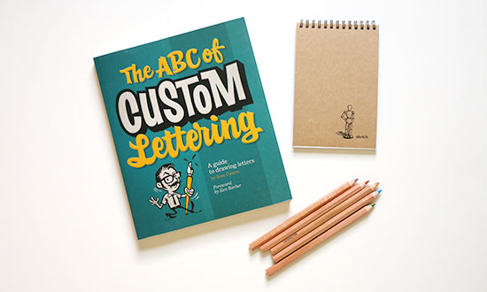 A lettering book, sketch book, and set of colors pencils on a white background.