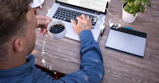 man writing on Macintosh computer, coffee cup