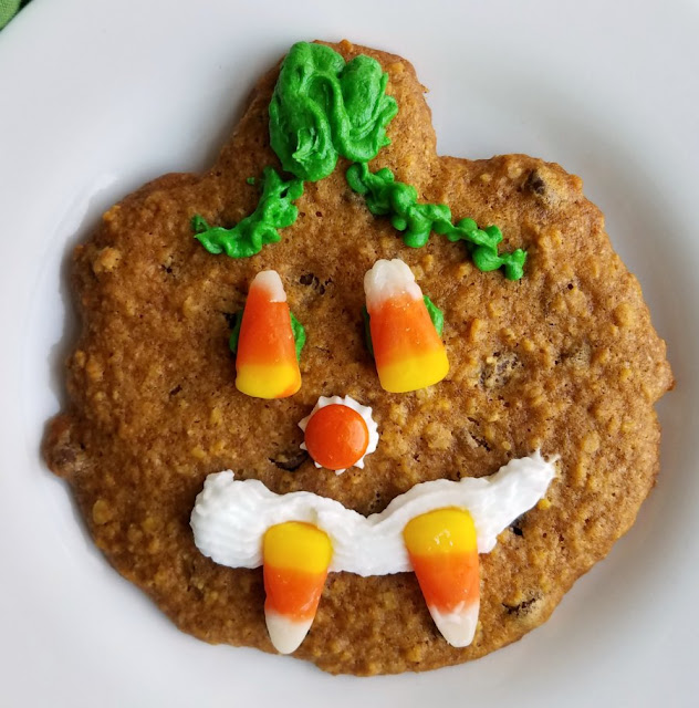 pumpkin shaped cookie with candy and frosting decoration to look like a jack-o-lantern