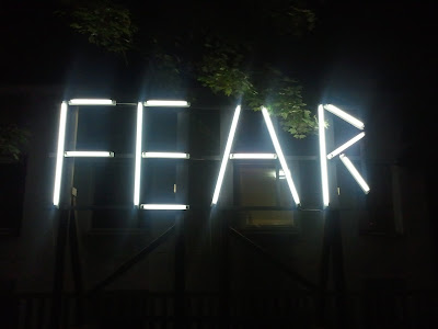 "A photo of an exhibit with lights where ""Fear"" is spelled out."