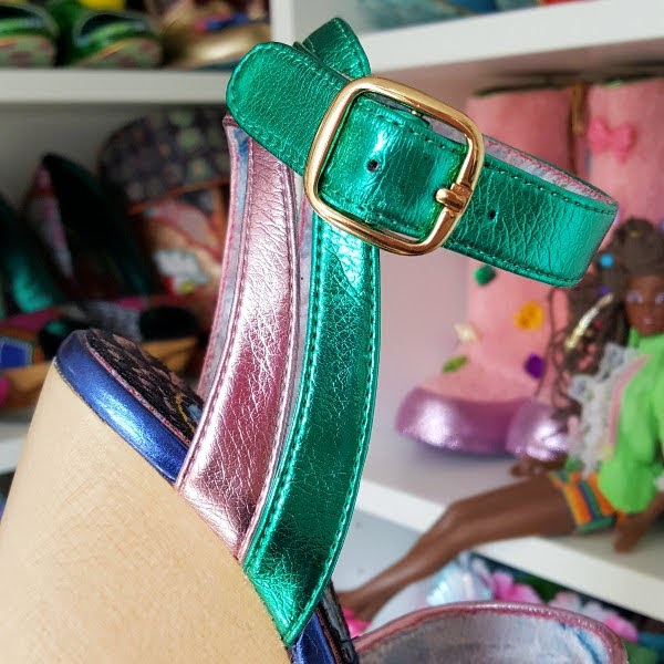 close up of metallic pink and green ankle straps on shoe with shoe shelves in the background
