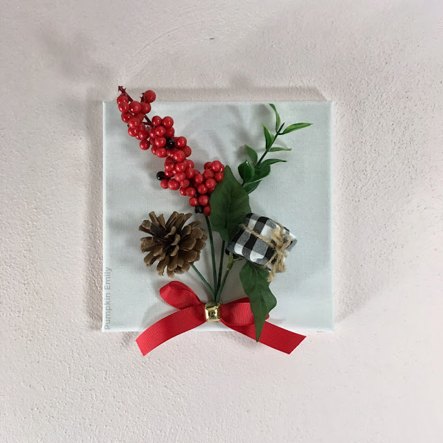 Christmas canvas with a flower pick on it