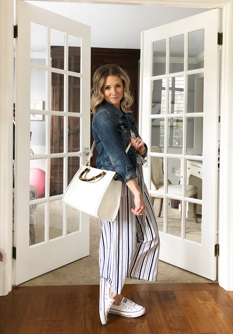 denim jacket with strip jumpsuit and white crossbody bag