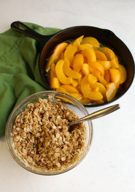 cast iron pan filled with peach slices and maple syrup with bowl of crisp topping nearby