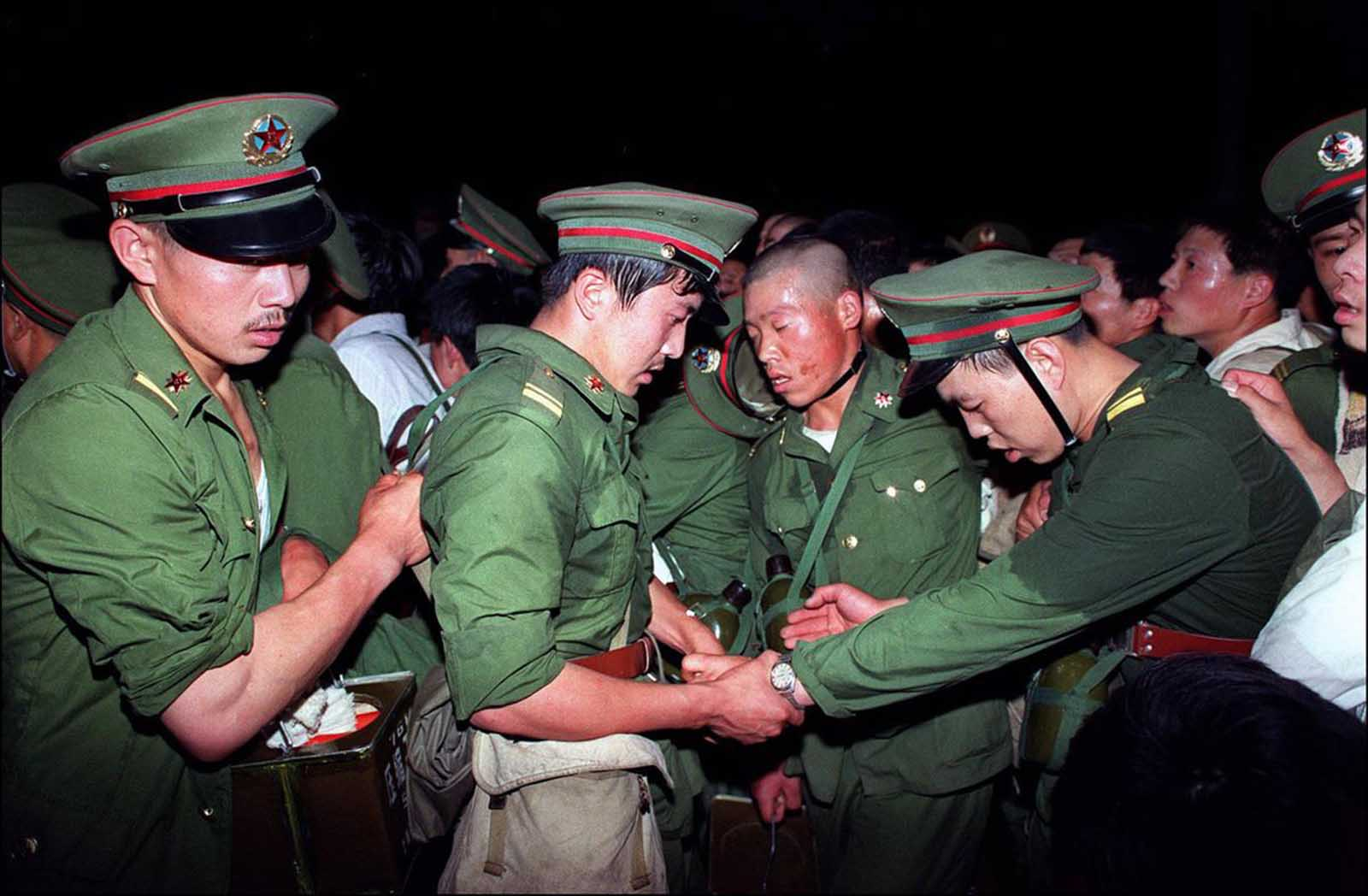 Exhausted, humiliated soldiers are hustled away by protesters in central Beijing, on June 3, 1989.