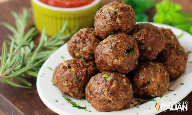 Baked meatballs on white plate with fresh herbs and sauce