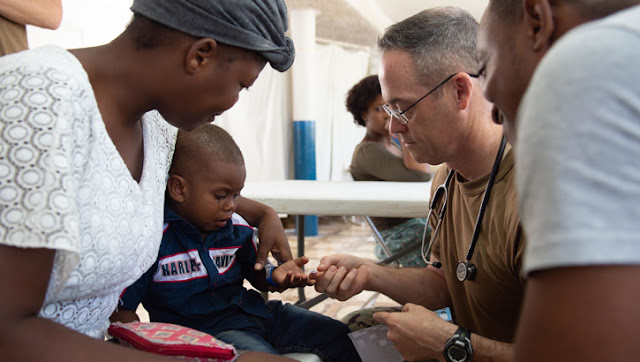U.S. Navy Capt. (Dr.) Michael Sullivan, a USU School of Medicine alumnus and pediatrician, gives a sticker to a two-year-old boy after examining his skin infection