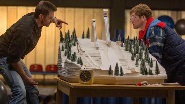 Hugh Jackman explicando el salto de esquí a Taron Egerton en una de las escenas