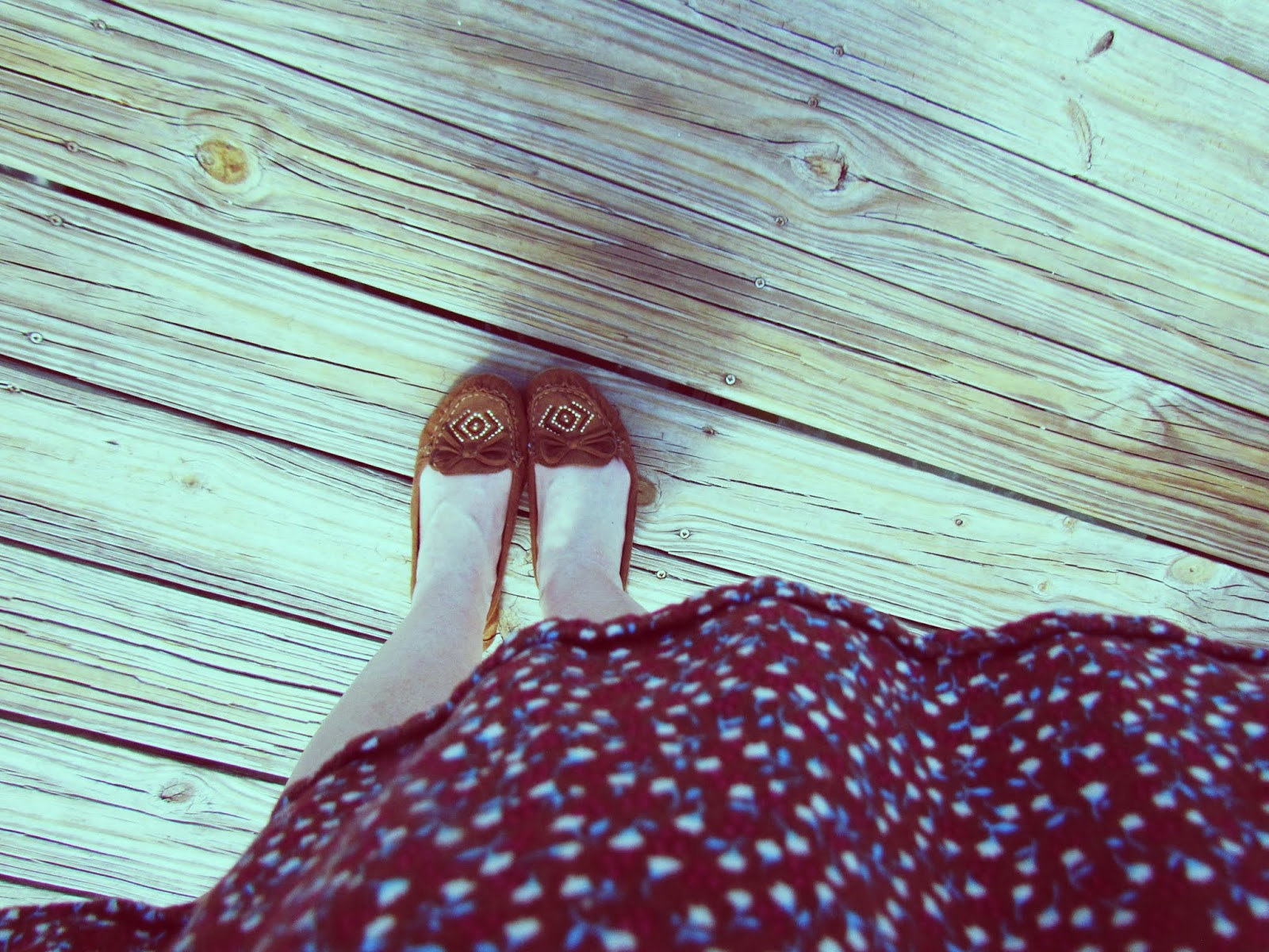 a woman wearing a brown flower-patterned dress and brown moccasins at the pier in Florida