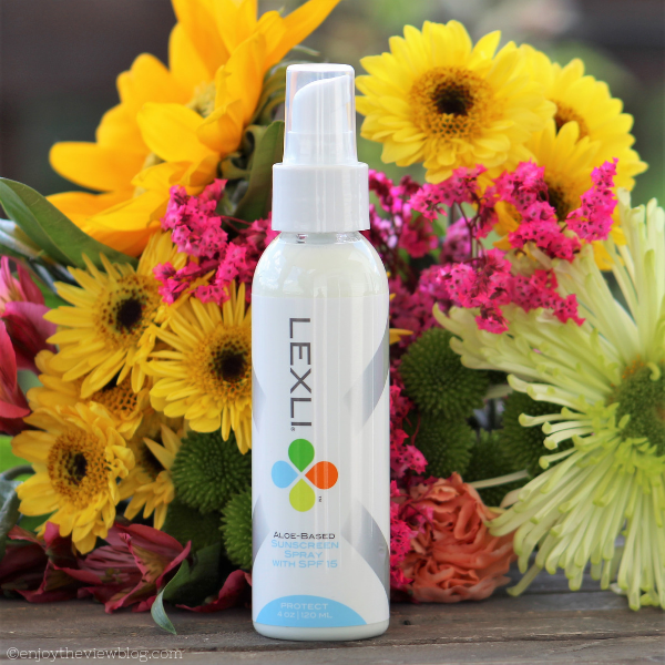 bottle of Lexli sunscreen spray sitting in front of yellow & pink flowers