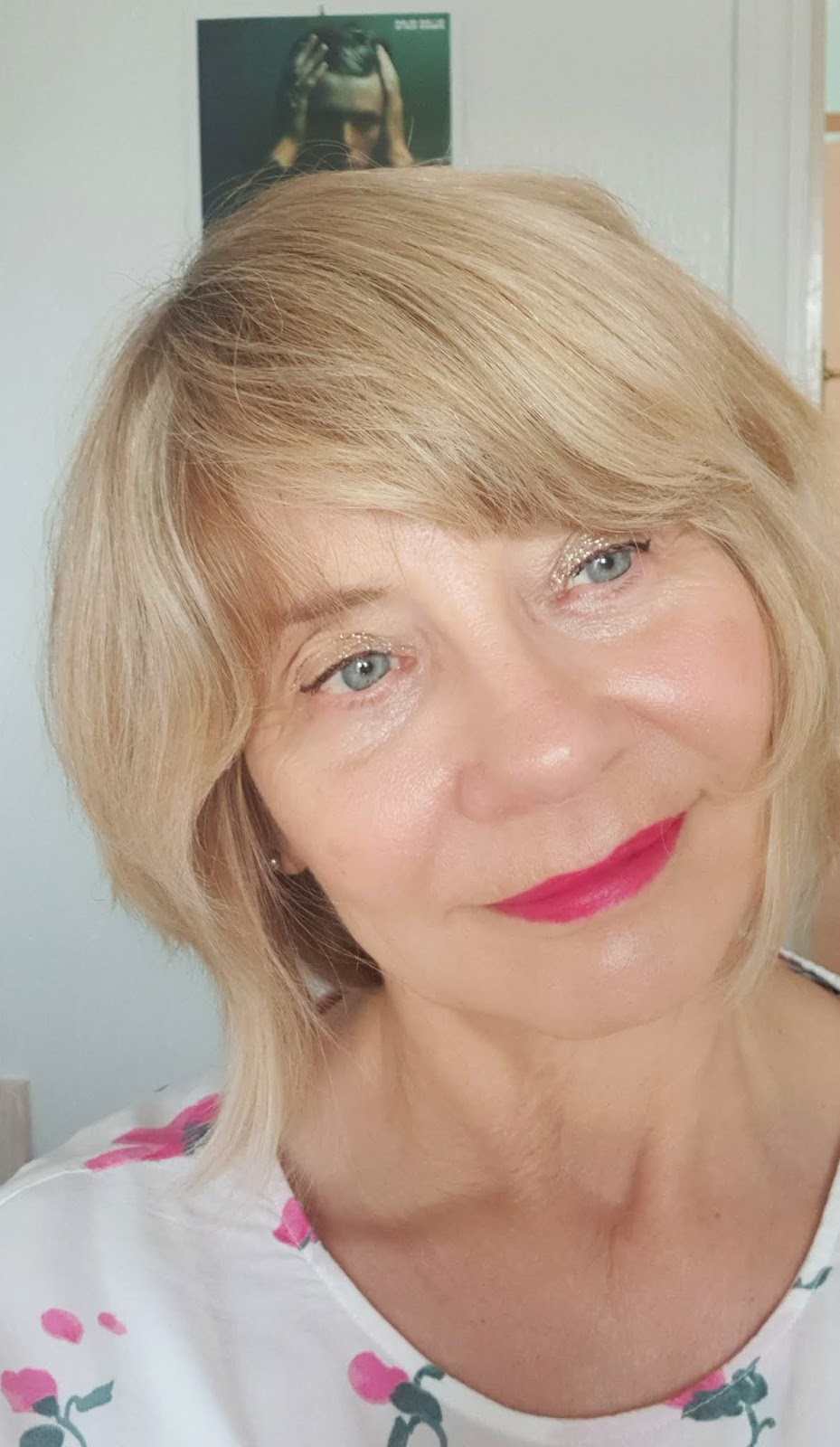 Over-50s woman with blonde hair, glitter eyeshadow and bright pink lipstick
