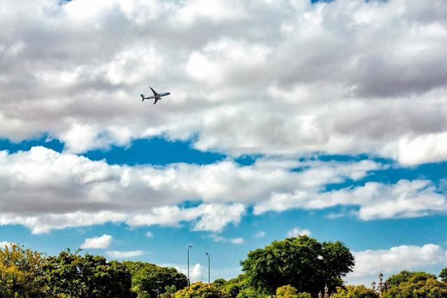 Un avión surca el cielo tapado por nubes blancas.