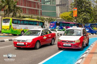 Kunterbunt! Taxis und Reisebusse in Kuala Lumpur.