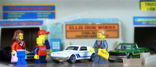 A lego car salesman approached a lego family