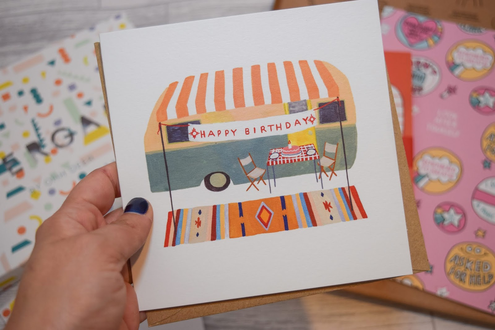 A hand holding a birthday card with a camper trailer and a happy birthday sign in front.