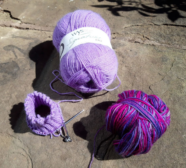 Image shows a partly knitted purple sock to the left, a ball of purple yarn in the centre to the back and a ball of purple variegated yarn to the right at the front.  All three items are sitting on a stone paving flag in the sunshine.