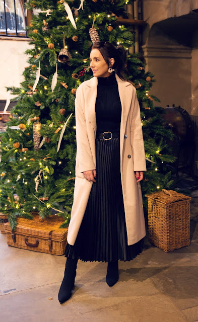 woman wearing cream coat in front of christmas tree