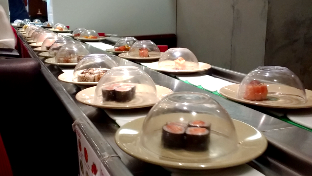 A lot of small plates with sushi in them rolling in a conveyor belt.