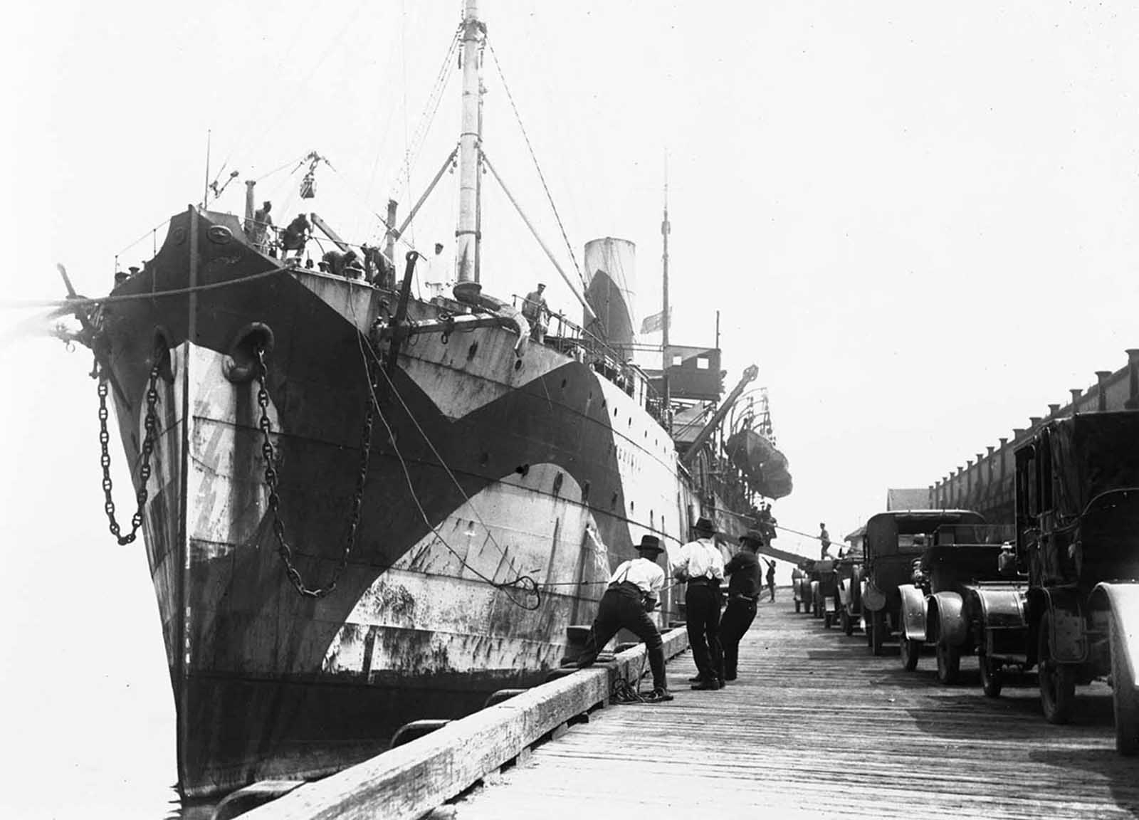 Troop transport Sardinia, in dazzle camouflage, at a wharf during World War I.