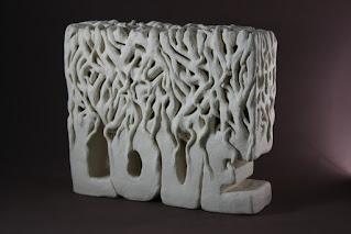 Escultura de cerámica con la palabra LOVE y raíces encima